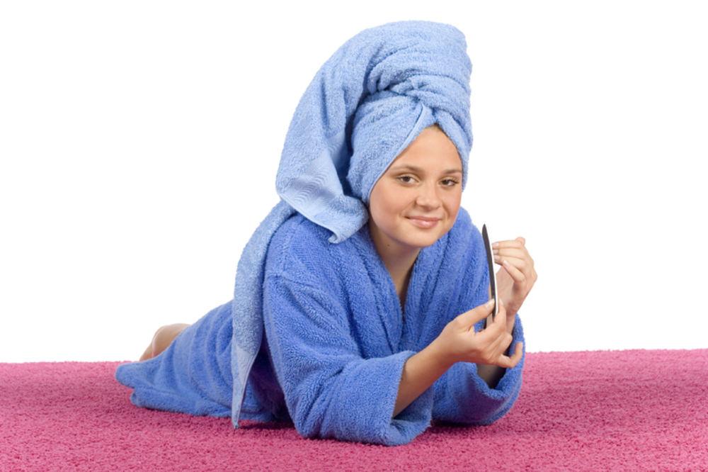 Девушка сушит волосы полотенцем